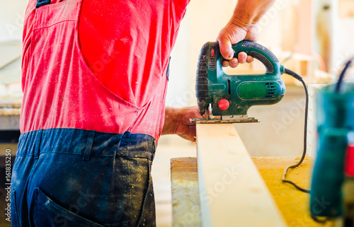 Close-up a man wearing workers uniform and cutting large wooden board in woodworking shop of furniture factory