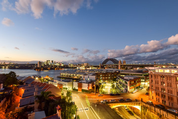 Stunning HDR night shot of the night skyline in Sydney, New South Wales, Australia. Beautiful view of the Sydney Harbour bridge, North Sydney, Millers Point and Walsh Bay. Shortly after sunset.