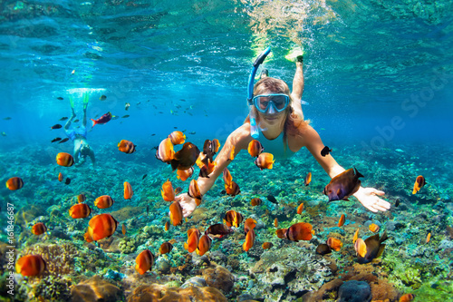 Happy family - couple in snorkeling masks dive deep underwater with tropical fishes in coral reef sea pool. Travel lifestyle, outdoor water sport adventure, swimming lessons on summer beach holiday