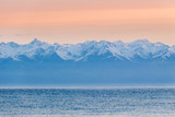 Issyk-Kul lake, snow-capped mountains and pink sky in the morning. Kyrgyzstan