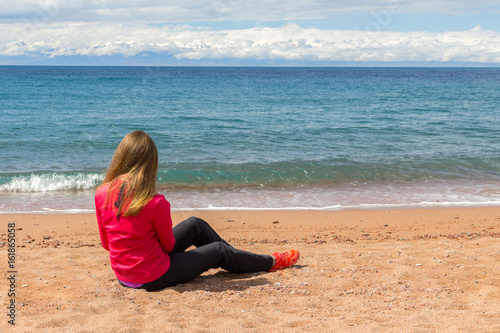 Lonely woman with long hairs sitting on a beach and looking on a lake Poster
