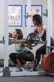 Personal trainer instructing woman about weight lifting with a barbell