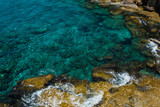 Crystal clear turquoise sea water background and rocky coast