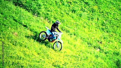 Slow motion shot of cross motorcycle moving downhill on the grass hill
