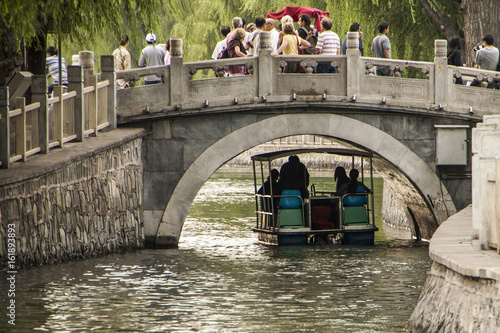 Unidentified people on stone arch bridge in Kumming Lake, Beijing, China, with boat beneath