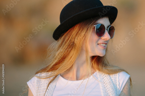 Poster Portrait of young pretty woman wearing hat and sunglasses outdoor on sunset