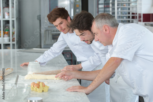 instructor in bakery teaching apprentice how to form a dough