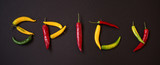 Peppers - word spicy written with fresh raw peppers