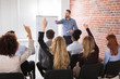 Group Of Businesspeople Raising Hands In Conference