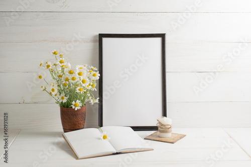 Daisy bouquet with open  notebook and motivational frame on background of  wooden planks in scandinavian style Photo by julia_arda