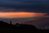 Beautiful sunset over mountains with storm clouds in background. Masivul Ceahlau, Romania.