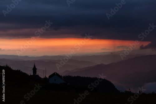 Beautiful sunset over mountains with storm clouds in background Poster