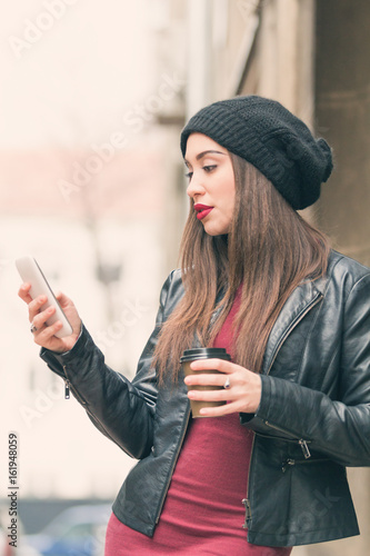 Poster Urban girl holding a cellphone and coffee outdoors.
