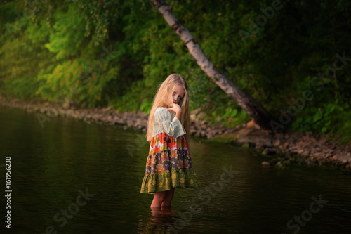 Beautiful fairy girl  with long hair standing in the river in a forest Poster