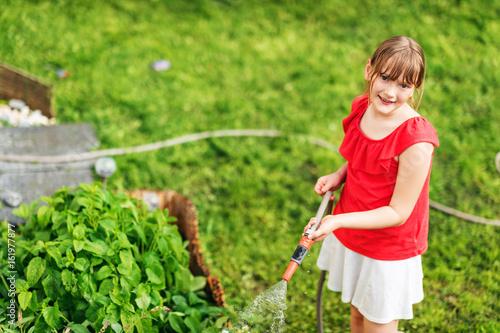 Kid girl watering plants in small garden, top view