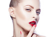 Close-up beauty face of woman touching her red lips. Professional bright make-up, clean skin