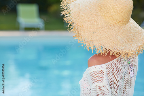 Image of a woman sitting by the pool side and smiling over her shoulder
