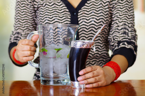 Foto op Canvas Buenos Aires Woman holding traditional mate cup with typical metal straw sticking up, south american herbal recreation drink