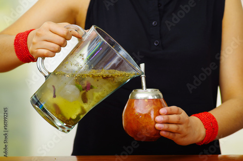Woman holding trasnparent jar containing water and green herbs, pouring into traditional cup with typical metal straw sticking up, preparing popular drink called mate
