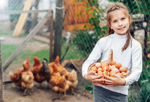 little cute girl holding in hands a basket full of fresh eggs. Plakat