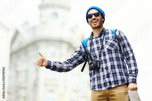 Backpacker with photocamera and map catching car in the city Poster