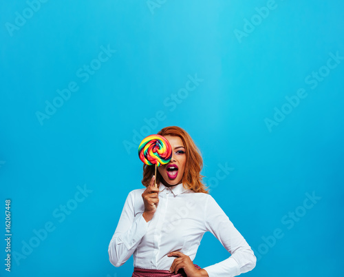 Beautiful young woman covering her eye with lollipop