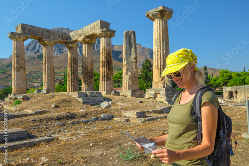 Tourism travel concept. Greece tourist female reads travel guide outdoors. Happy woman holding informative guide at Doric Temple of Apollo in Ancient Corinth, Peloponnese. Acrocorinth on background.