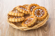 Cookies with jam in wicker basket on table