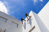 industrial alpinist work on white wall - 162073610