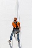 industrial alpinist work on white wall - 162074016