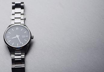Metallic wristwatch on gray background. Copy space.