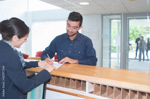 male guest filling up a formular at hotel counter