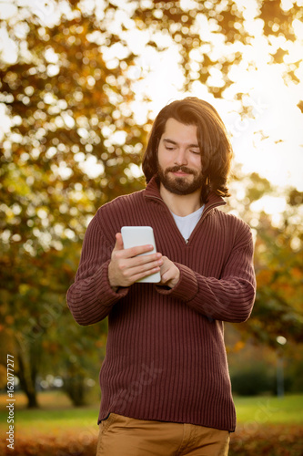 Young man using cellphone in the park with autumn / fall colors. Poster