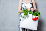 woman holding bag with organic herbs and vegetables - 162085008