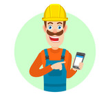 Builder pointing at mobile phone in his hand - 162103806