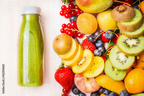 Green smoothie or juice with various fruits and berries ingredients on white wooden background, top view