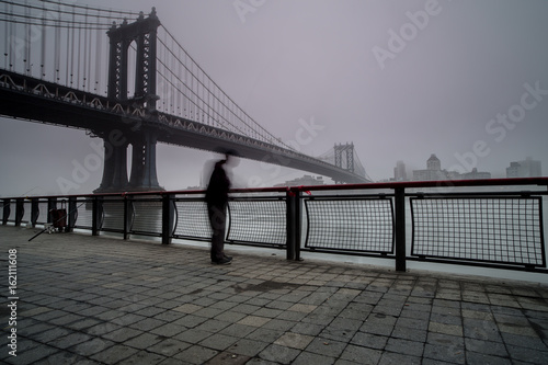 Man fishing in hudson river near Manhattan bridge, on a foggy morning плакат
