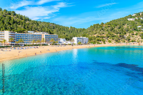 Azure sea water and hotel buildings on beach in Cala San Vicente bay, Ibiza island, Spain