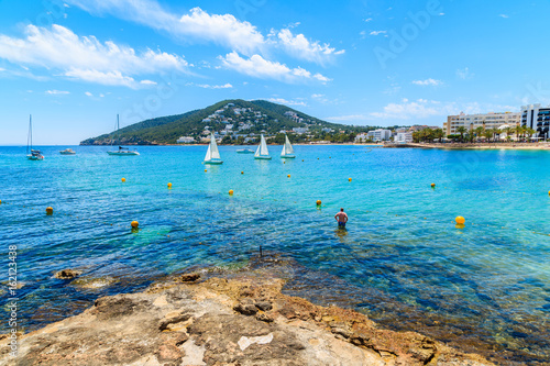 Unidentified man standing in water on Santa Eularia beach, Ibiza island, Spain