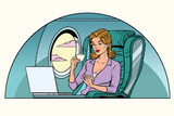 Fototapety Businesswoman in business class of the aircraft works at a lapto