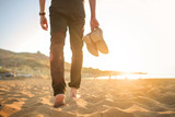 Man walking in the beach, he is holding his pair of shoes. - 162128285