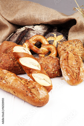 Different kinds of bread rolls on white board from above. Kitche