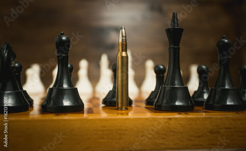 Big riffle bullet among chess pieces. Concept of weapon power © Кирилл Рыжов