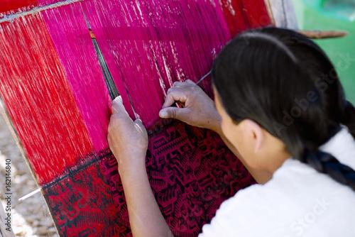 Native Peruvian woman weaving intricate llama wool garments using a traditional Poster