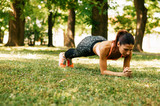 Fit young woman doing the plank exercise in park - 162160850