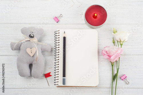 Blank notebook, cup of coffee, lit candle, flowers