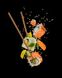 Sushi pieces placed between chopsticks on black background © Jag_cz