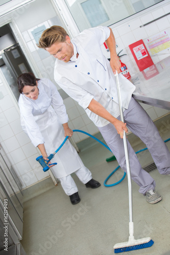 restaurant employees cleaning the kitchen floor