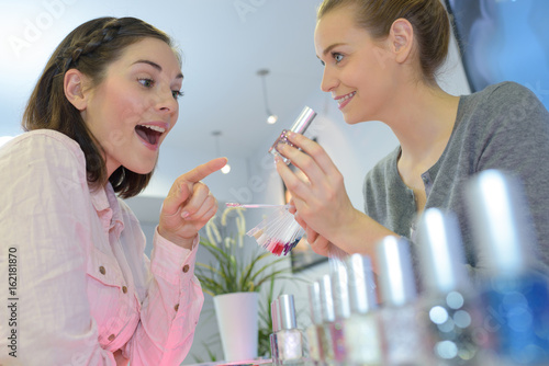 Poster young woman chooses perfume in the shop