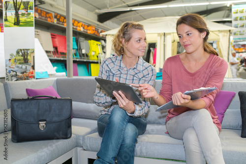 two girls using tablet and taking note on clipboard Poster